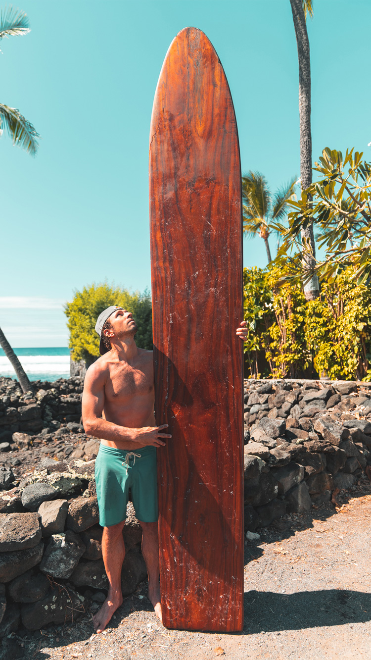 Hawaii: Hugo Pinheiro stands next to an ancient wooden surfboard | Photo: Red Bull