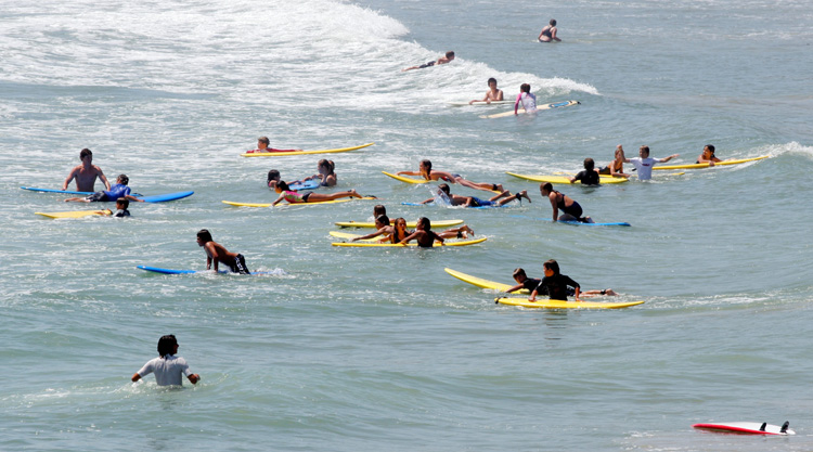 Beginner surfers: learning how to surf includes staying safe in the water | Photo: Shutterstock
