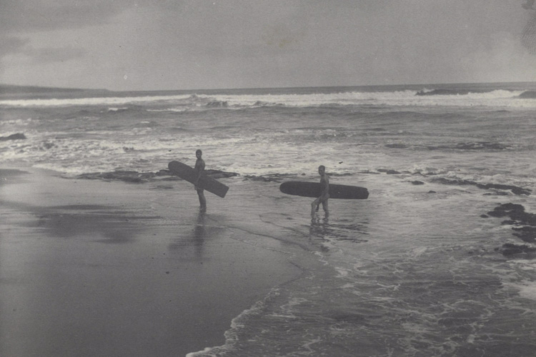 Hawaii, 1890s: two Polynesian natives carry their surfboards on a sandy beach at Hilo Bay | Photo: Herbert Smith