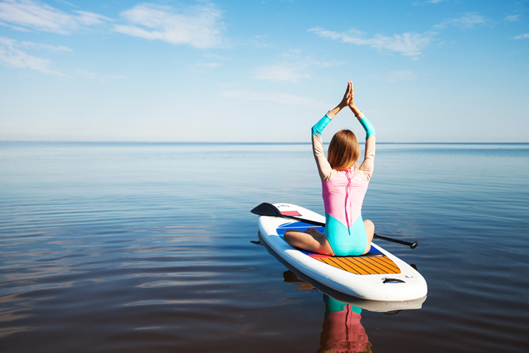 SUP Yoga: performing yoga poses on a stand-up paddleboard | Photo: Shutterstock