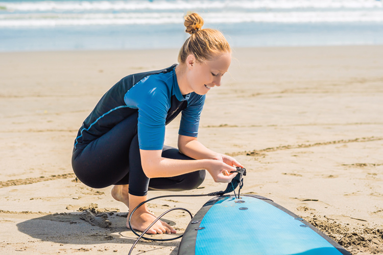 Surfboard leash string: learn how to insert it push it through the leash plug | Photo: Shutterstock