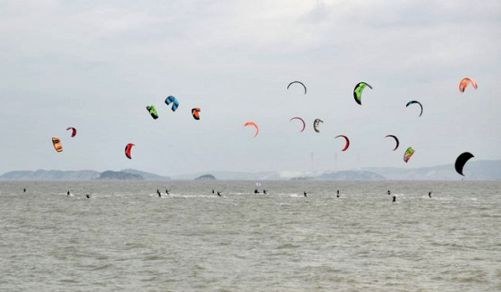 Xiamen Long Distance Kitesurfing Race: coloured fleet in grey sky